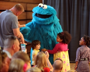 Cookie Monster, a philosophical Muppet who now enjoys cookies in addition to a well-balanced diet, comes out to greet Marine families during a USO performance of Sesame Street Live aboard Marine Corps Air Station New River, April 28. During the show, Cookie Monster gave advice to Marine families about moving away from friends.